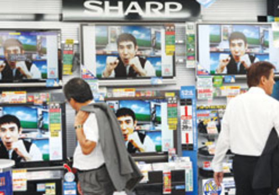 A shopper looks at Sharp flat-panel TVs at an elec