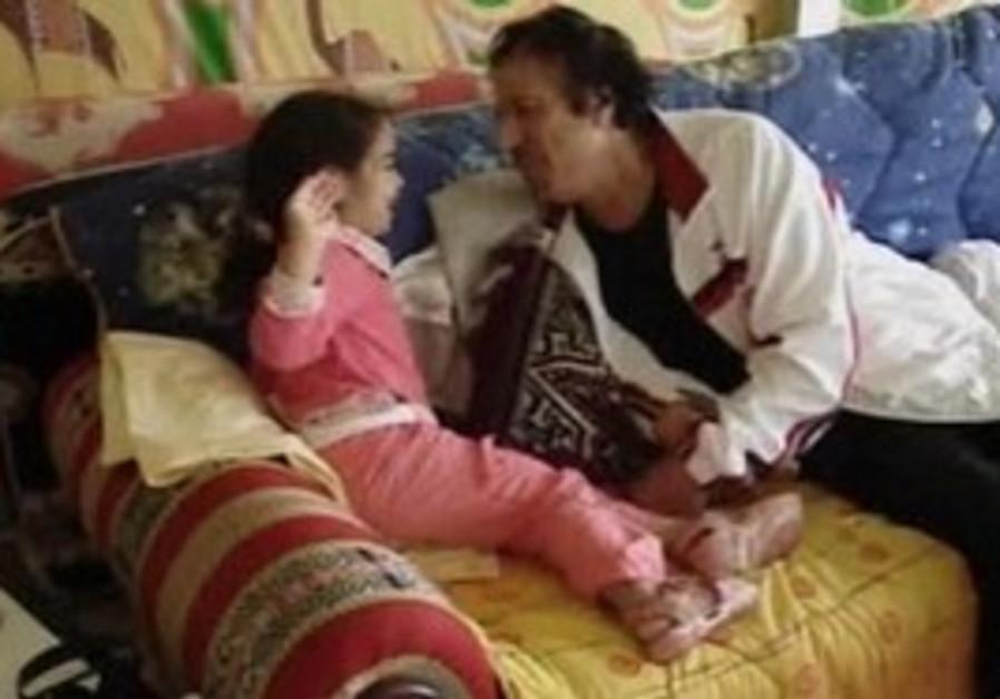 Muammar Gaddafi lovingly plays with granddaughter.