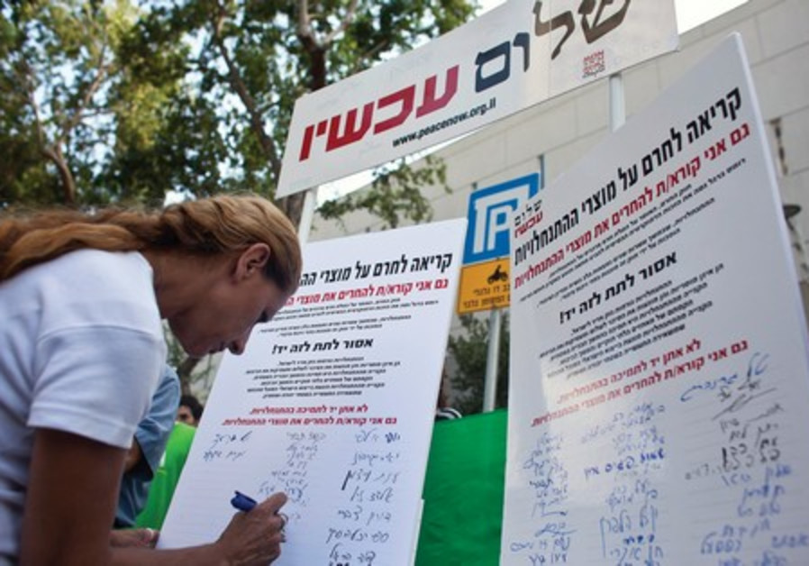 A woman signs a Peace Now petition