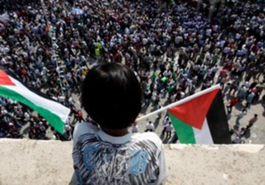 Palestinian boy waves flag  at rally in Ramallah