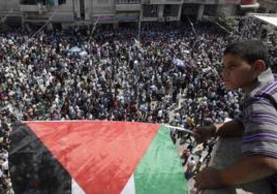 Palestinian boy looks over rally in Ramallah
