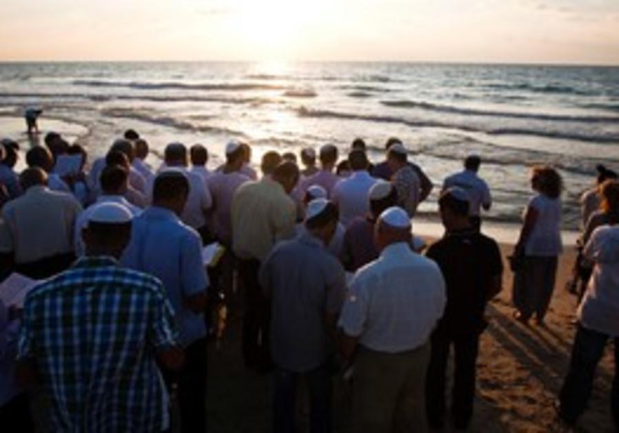People take part in the Tashlich ritual on beach