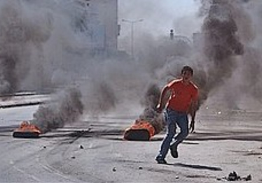 A Palestinian youth runs next to burning tires dur