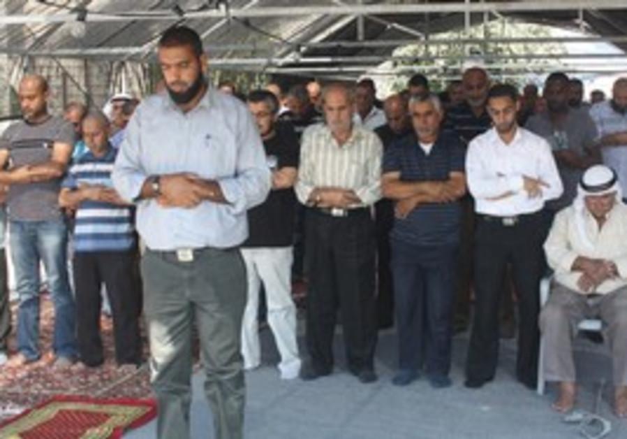 Tuba Zanghariya men pray outside bured mosque