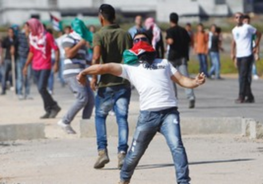 Man throws a stone at soldiers in Ramallah