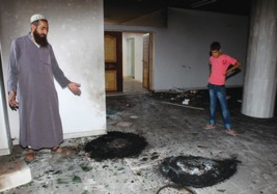 Palestinians look at burned tires in mosque