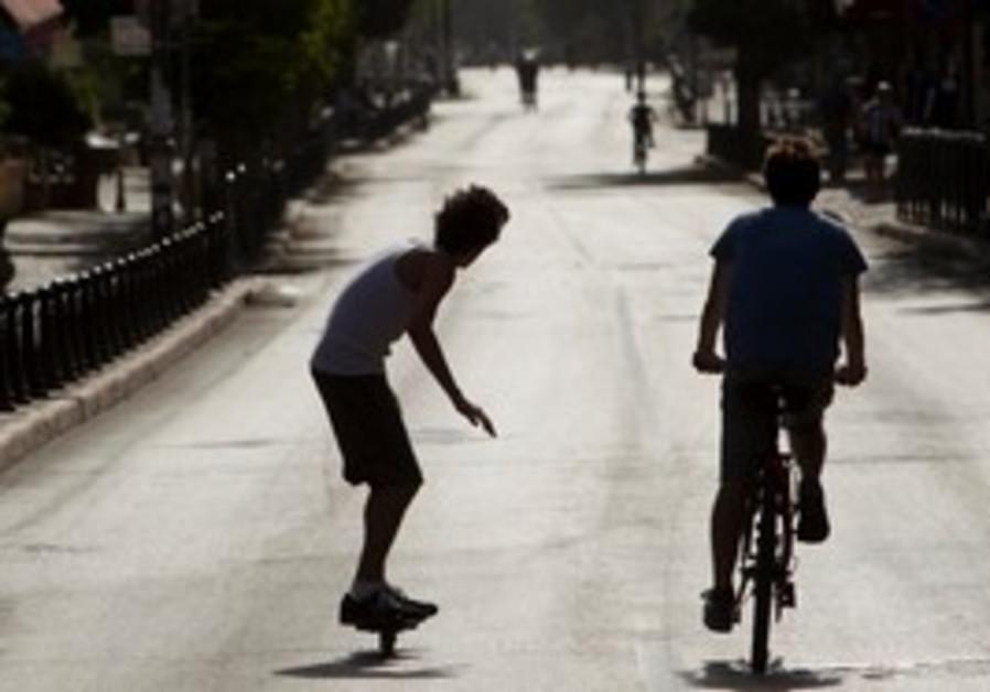 Youths ride on bikes during Yom Kippur