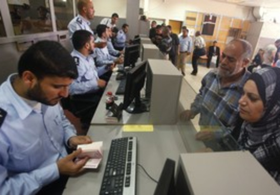 Hamas policeman checks passport at Rafah border