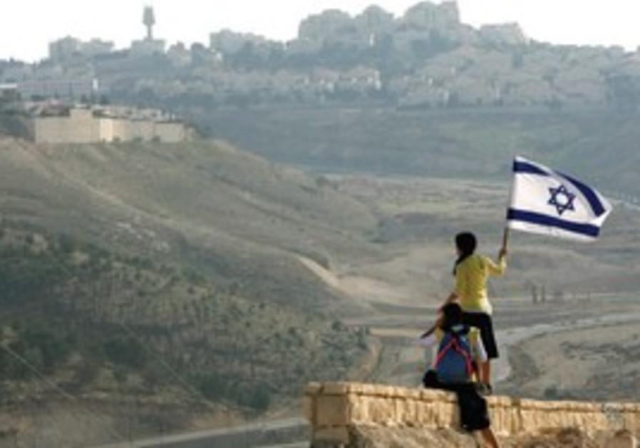 Girls hold Israeli flag near Maale Adumim.