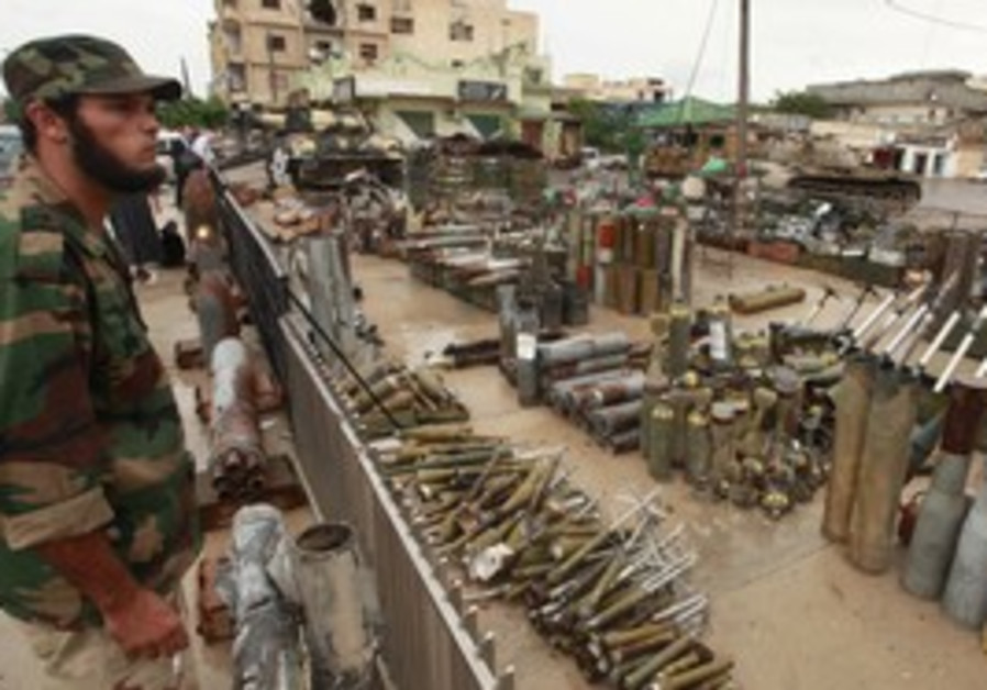 Anti-Gaddafi fighter looks at weapons left by Gadd