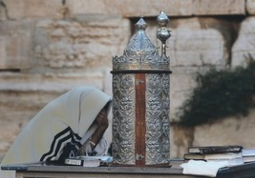 Man praying with Torah at Kotel.
