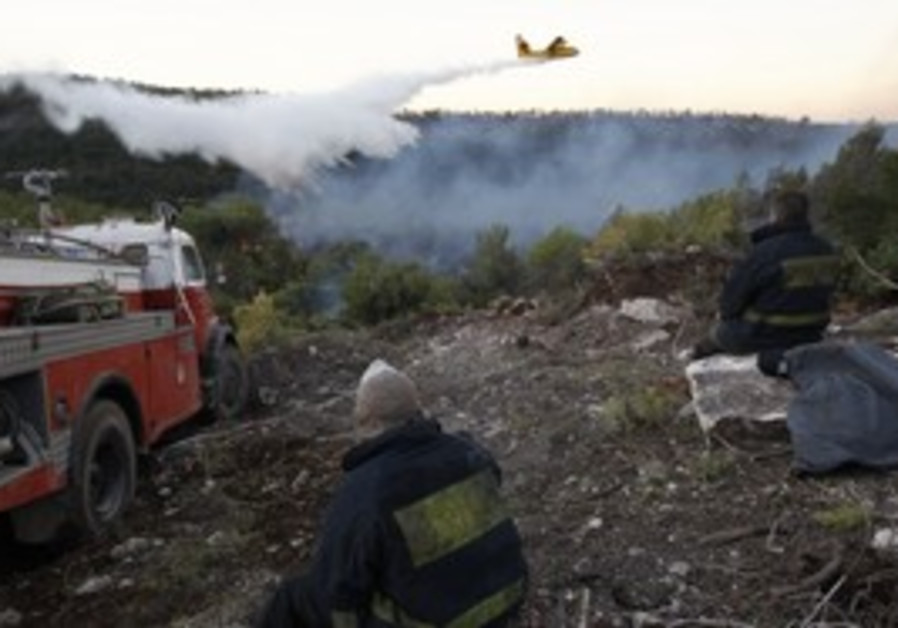 Firefighter watches water-dropping plane [file]