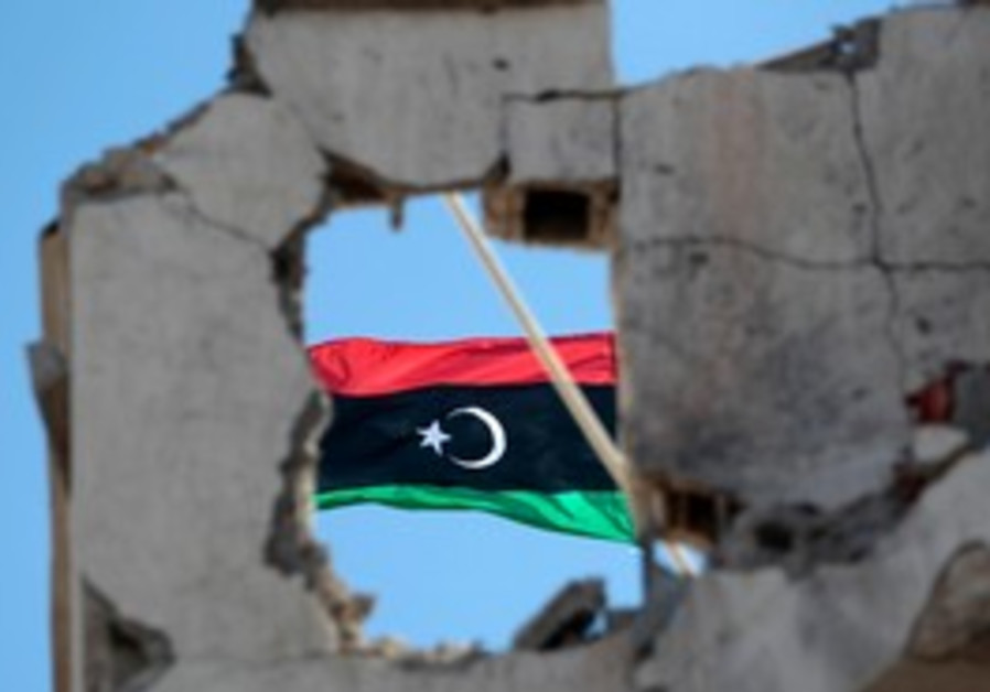 Libya flag seen on top of a damaged building