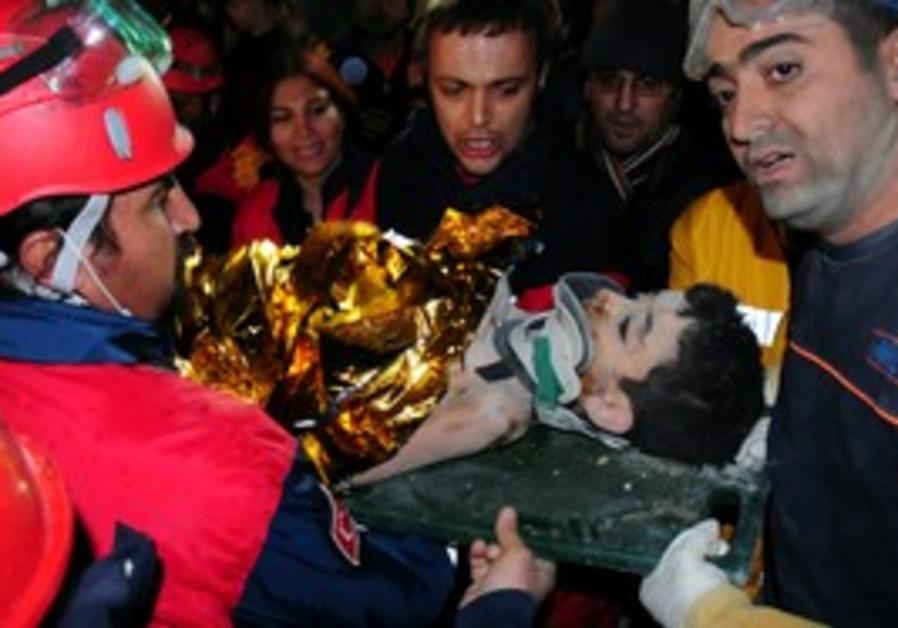 Turkish emergency service workers carry survivor