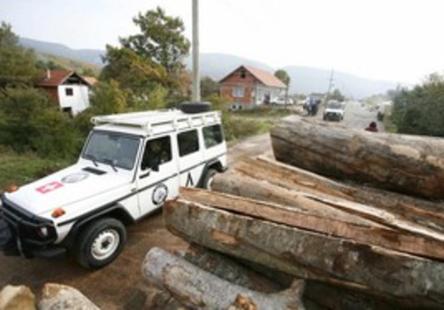 A KFOR vehicle passes roadblock in Kosovo.