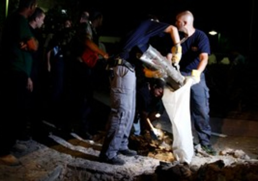 Police officiers remove the remains of Grad rocket