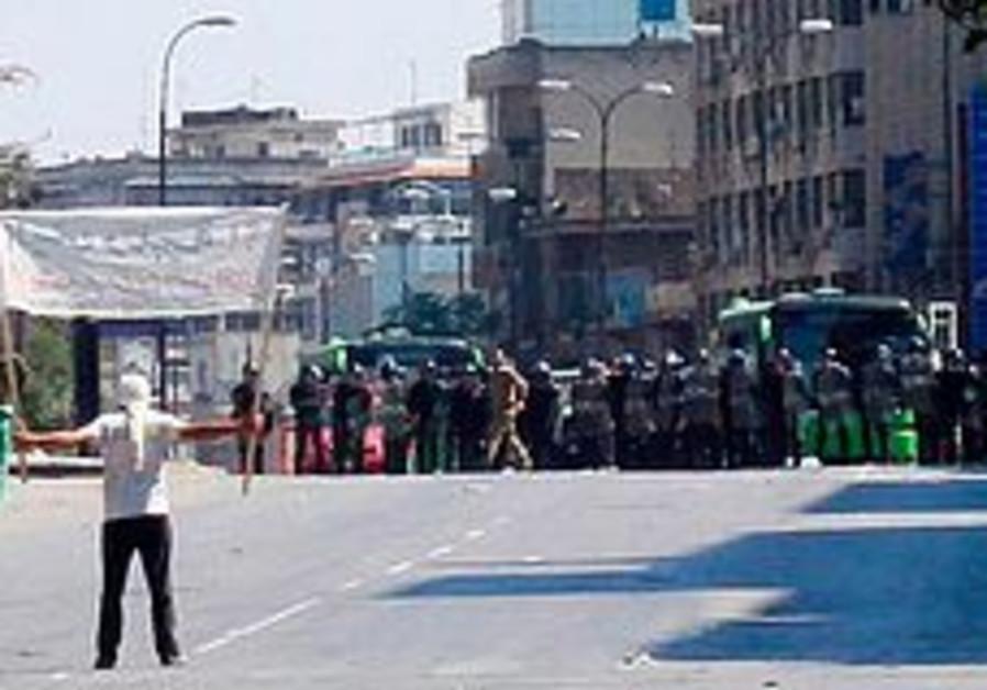 A protester faces riot police at Khalidia, near Ho
