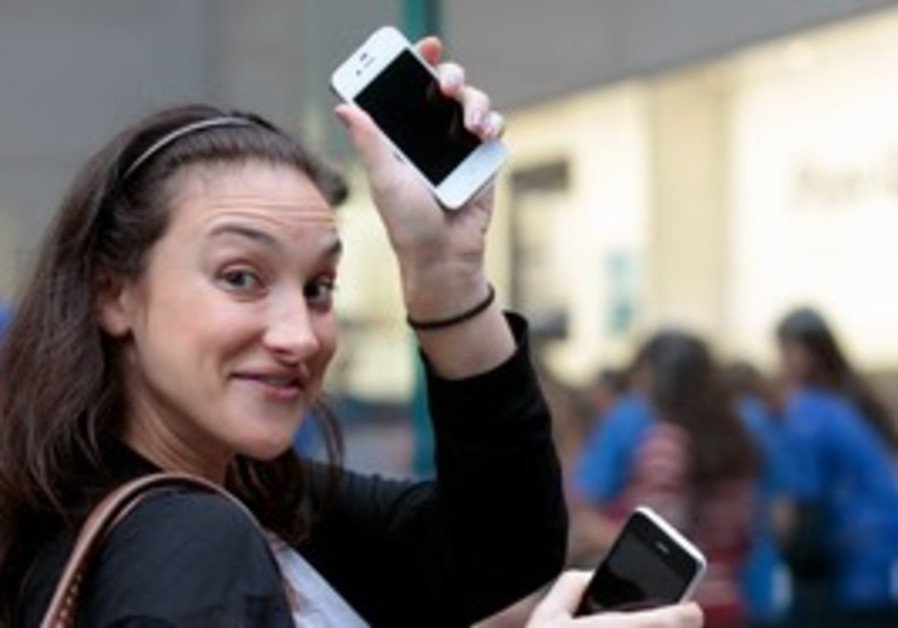 A woman showing off her new iPhone 4s in NY