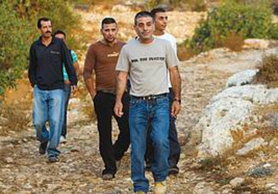 PALESTINIANS WALK through the West Bank village of