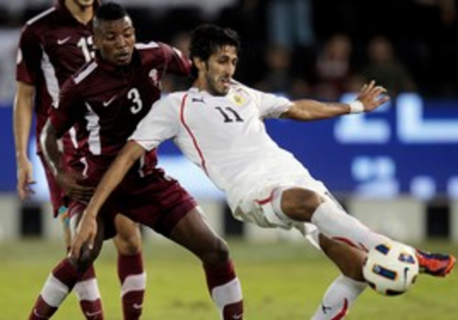 Qatar's Mohammed Kassola (L) fights for the ball