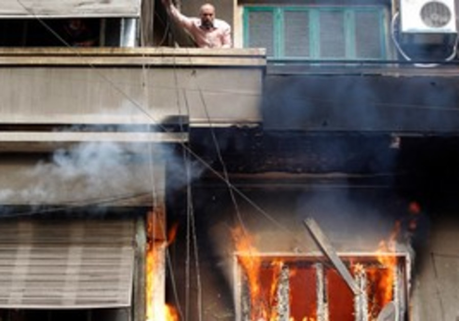 Protester stands in burning building in Cairo