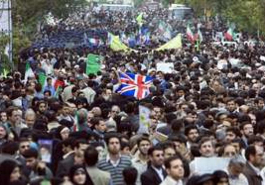 Iranian demonstrators carry a British flag