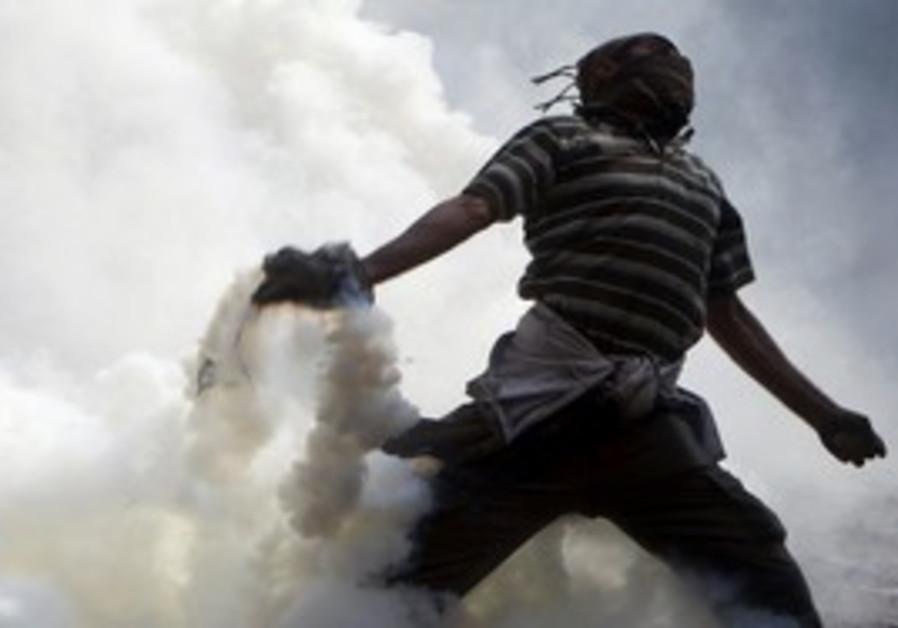 Protester throws tear gas back near Tahrir.