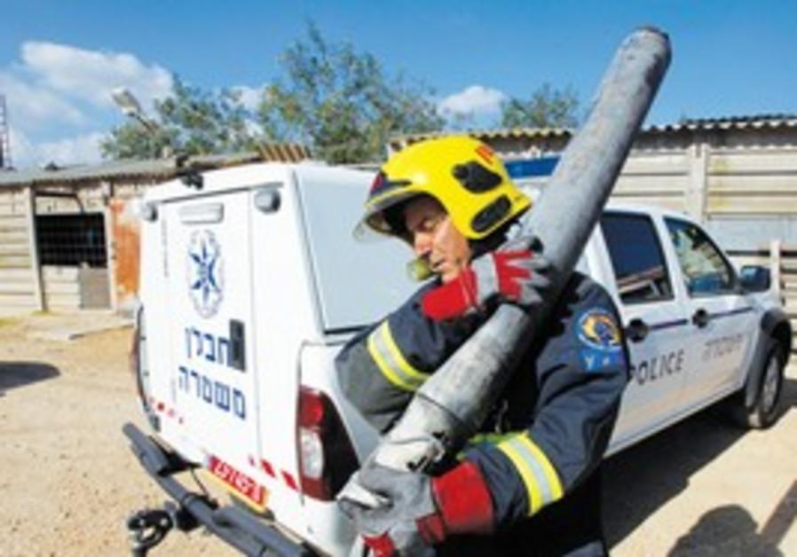 Firefighter carries remains of Katyusha rocket