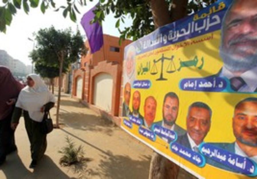 Egyptian women walk past Muslim Brotherhood poster