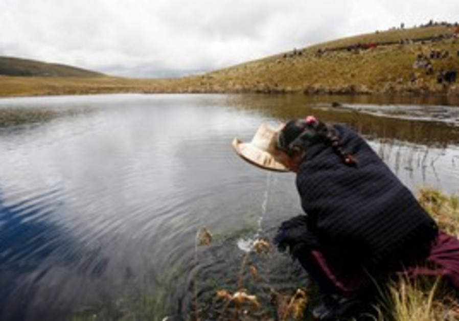Andean woman drinks water from Cortada lagoon