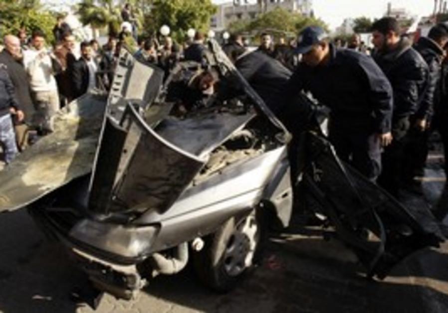 Hamas security forces survey car hit in IAF strike