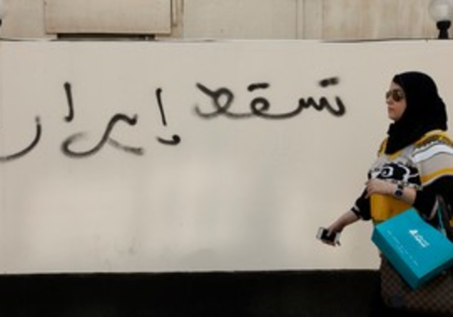 Woman walks past anti Iran graffiti