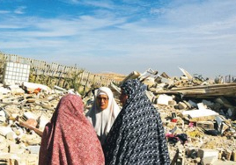 Palestinians stand near razed home in e. J'lem