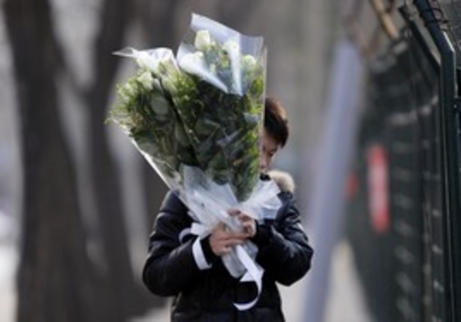 A North Korean man holds flowers, Beijing, Monday