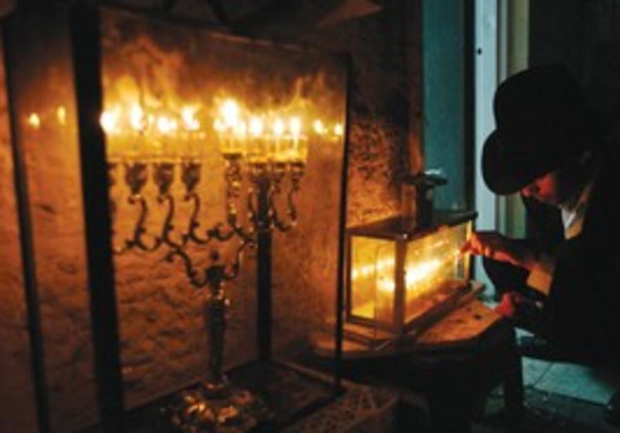 Orthodox Jew lighting menorah on Hanukkah