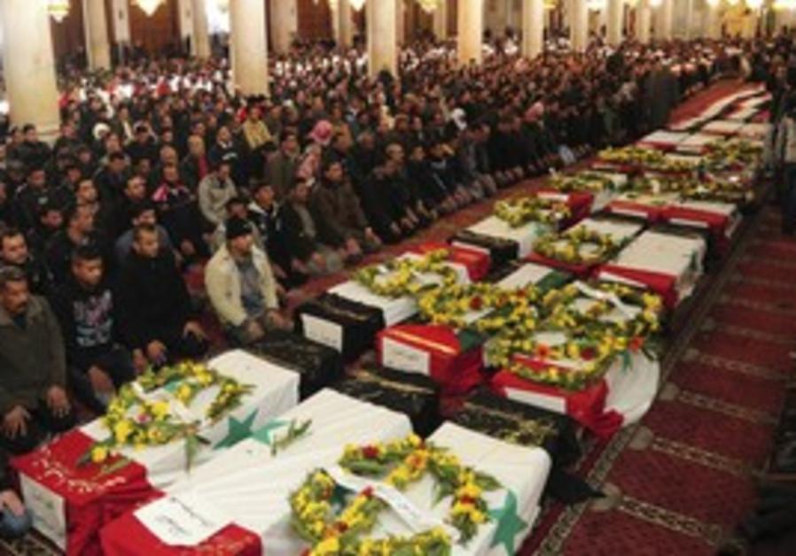 Syrians pray next to coffins