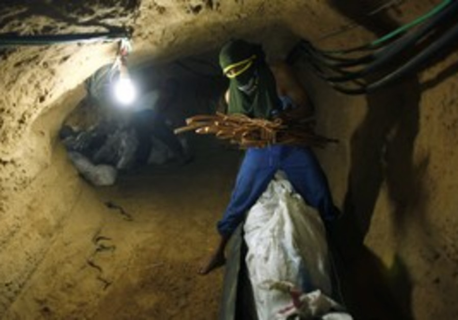 A Palestinian transports goods in a tunnel.