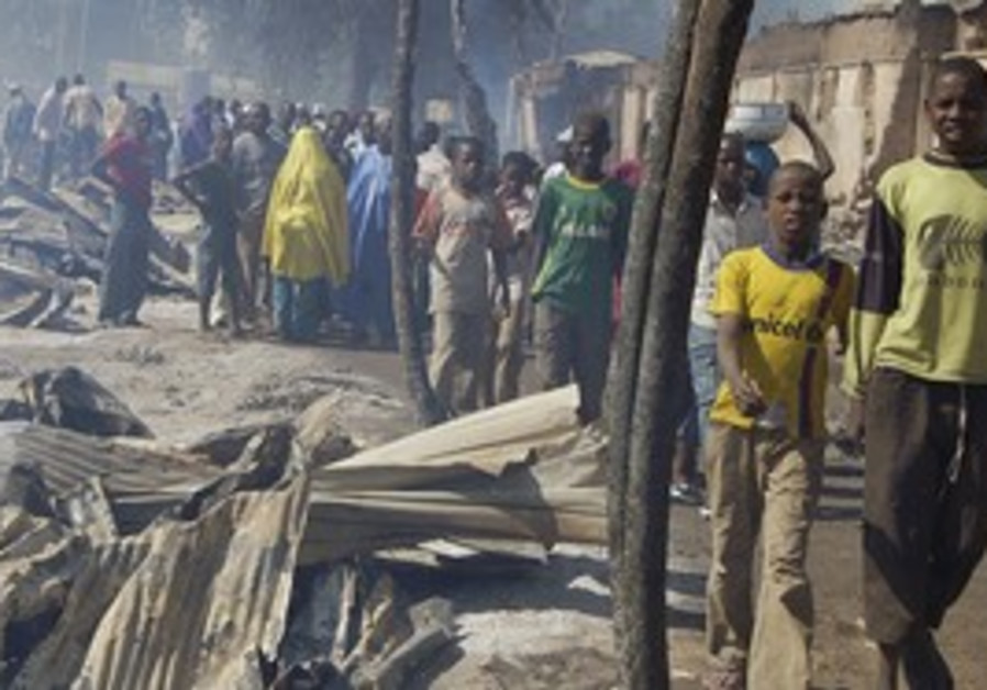 Nigerians walk by after fire razes market