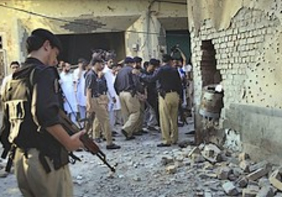 Pakistan police officers examine the site of a sui
