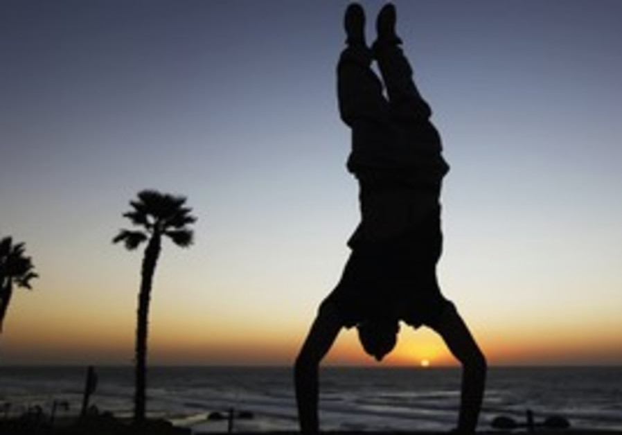 Youth does a handstand on the beach in Netanya
