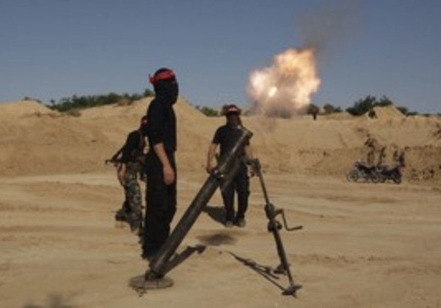 Palestinian terrorists fire a mortar shell in Gaza