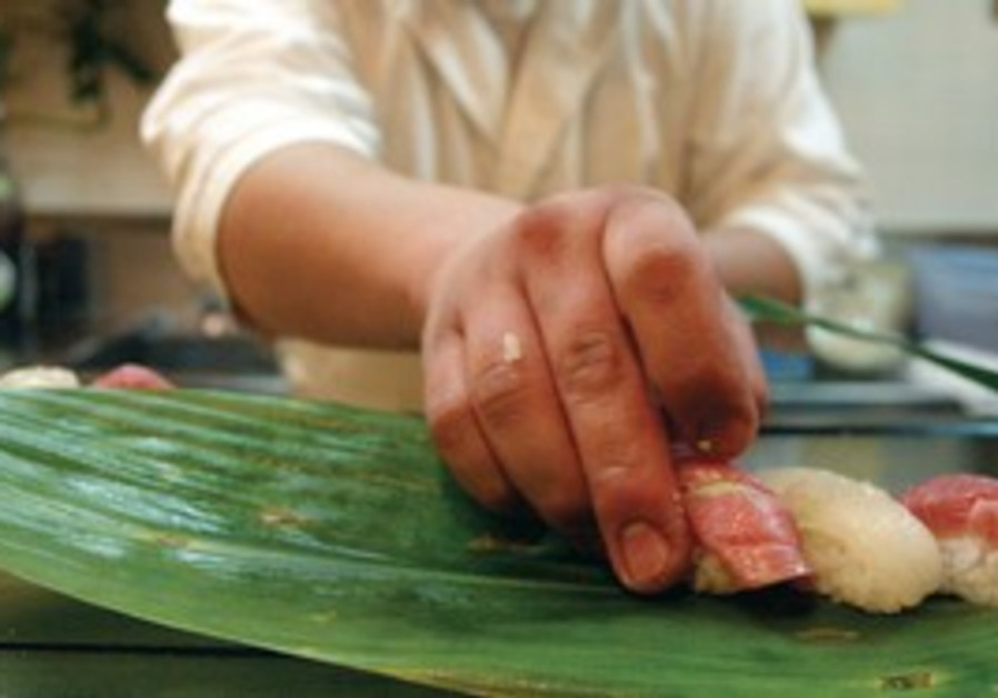 sushi chef prepares sushi