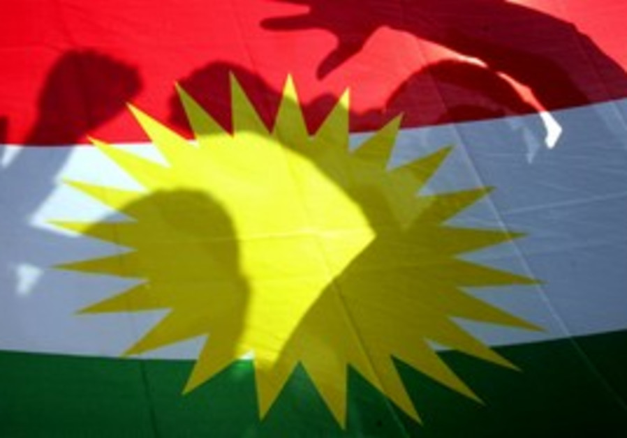 Kurds pose behind Kurdish flag