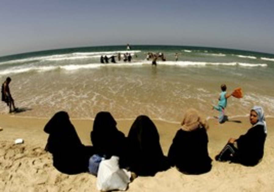 Palestinian women sit at Gaza Strip beach