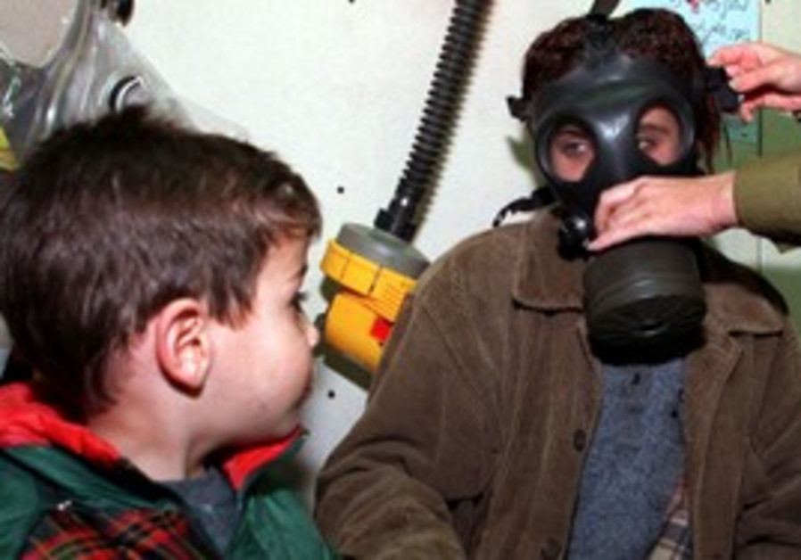 Boy watches as mom is fitted for a gas mask