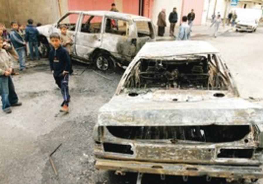 Palestinians near damaged cars