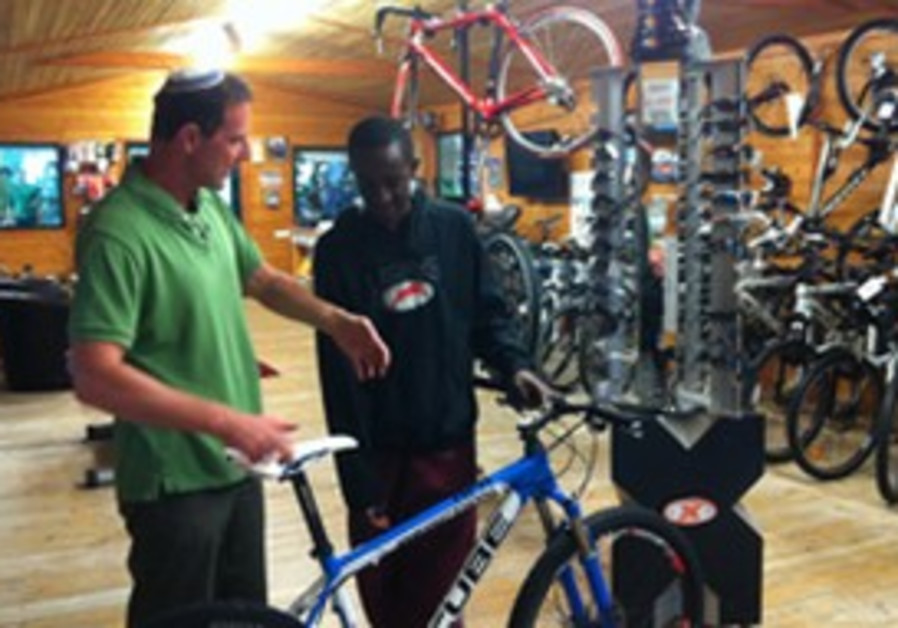 Chaim Wizman (left) shows a bicycle to a customer