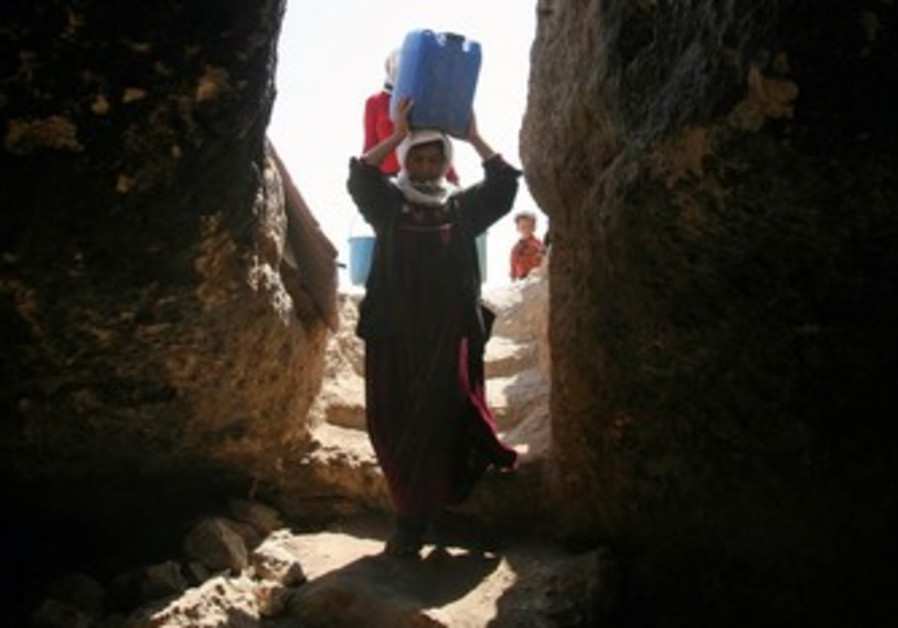 Palestinian woman carrying water