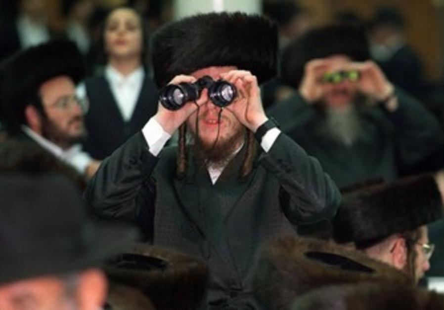 An Orthodox Jew looks through binoculars
