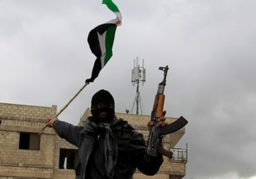 A defected Syrian soldier holds a rifle and flag
